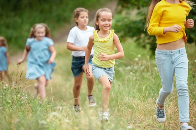 緑の牧草地で走っている子供たち