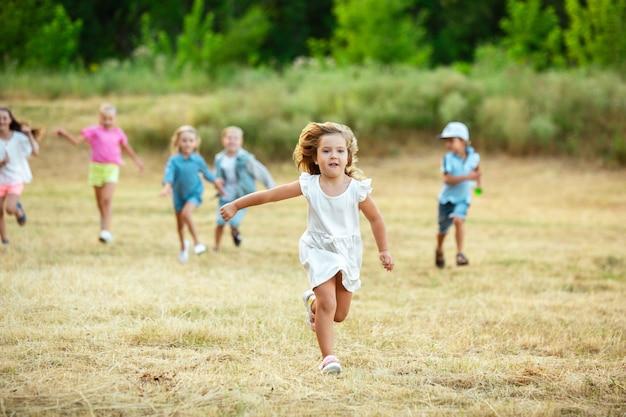 Дети, дети бегают по лугу в лучах летнего солнца. выгляди счастливым, жизнерадостным, с искренними яркими эмоциями. симпатичные кавказские мальчики и девочки. понятие детства, счастья, движения, семьи и лета.