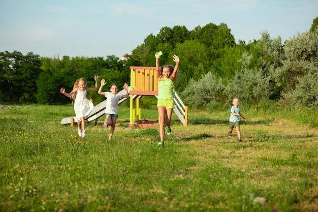 子供たち、夏の日差しの中で牧草地を走っている子供たち。誠実な明るい感情で幸せに、陽気に見えます。かわいい白人の男の子と女の子。子供の頃、幸福、動き、家族と夏の概念。