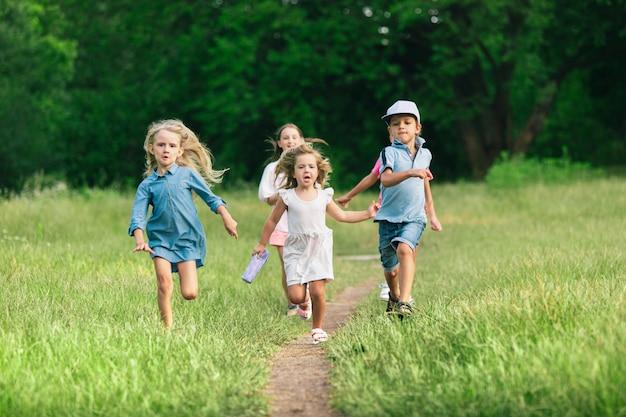 子供たちは、夏の日差しの草原で走っている子供たち。