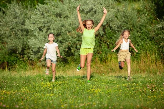 夏の日光の下で牧草地で走っている子供たち