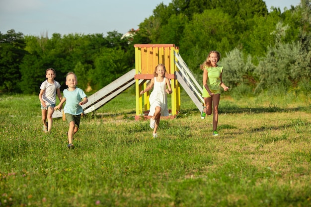 子供たち、牧草地で走っている子供たち