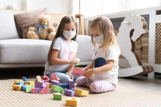 Дети дети в масках для защиты covid-19, играя в игрушки в игровой комнате. оставайтесь дома на карантине для предотвращения пандемии коронавируса