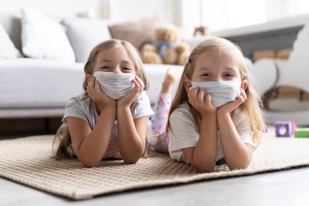 Дети дети в маске для защиты covid-19, играя в гостиной. оставайтесь дома на карантине для предотвращения пандемии коронавируса