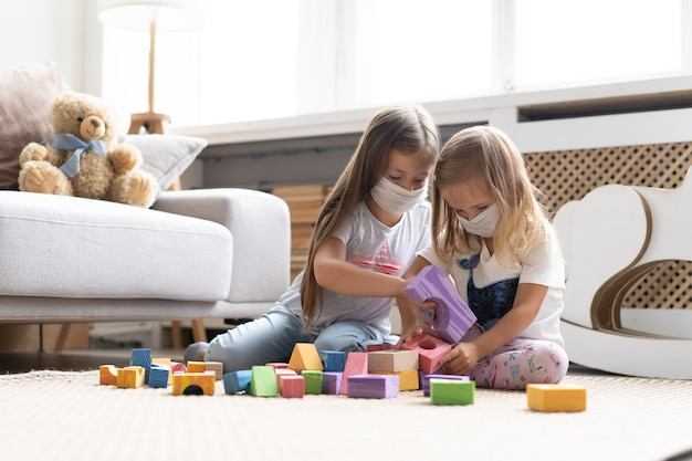 Kids children wearing mask for protect covid-19, playing block toys in playroom. stay at home quarantine for coronavirus pandemic prevention