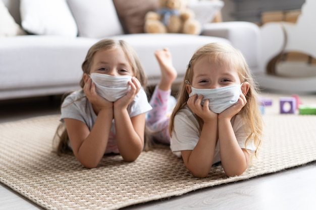 Kids children wearing mask for protect covid-19, playing in living room. stay at home quarantine for coronavirus pandemic prevention