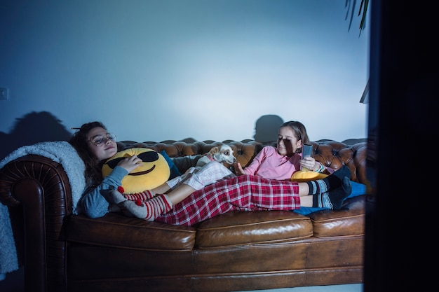 Kids chilling on sofa with dog