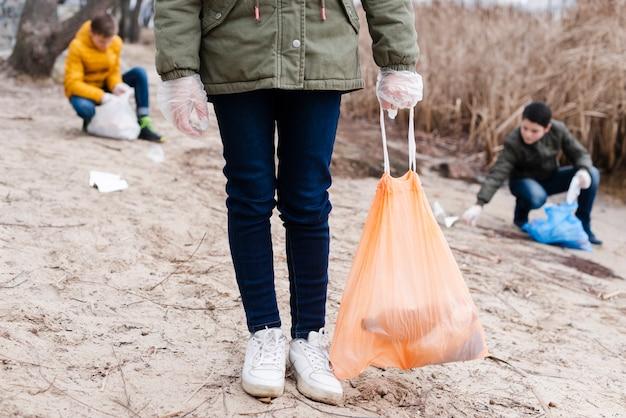 Bambini che puliscono il suolo e riciclano