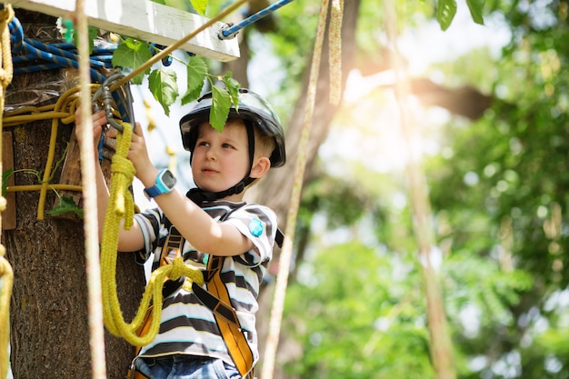 アドベンチャーパークに登る子供たち。少年はロープコースの冒険で登山を楽しんでいます。ハイワイヤーパークを登る子供