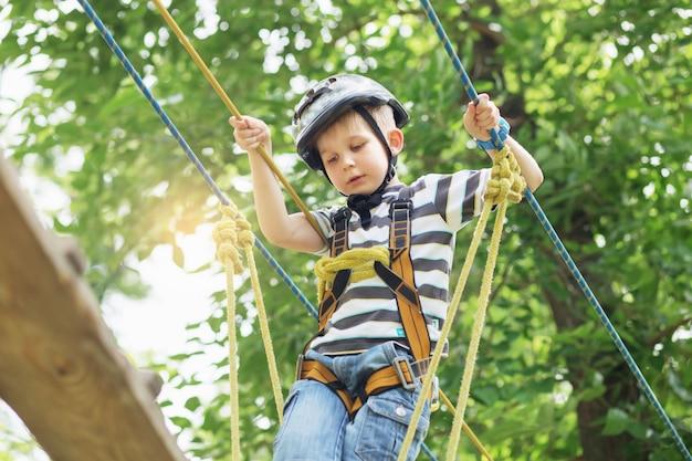 모험 공원에서 등반하는 아이들. 소년은 로프 코스 모험에서 등반을 즐깁니다. 하이 와이어 파크를 등반하는 어린이