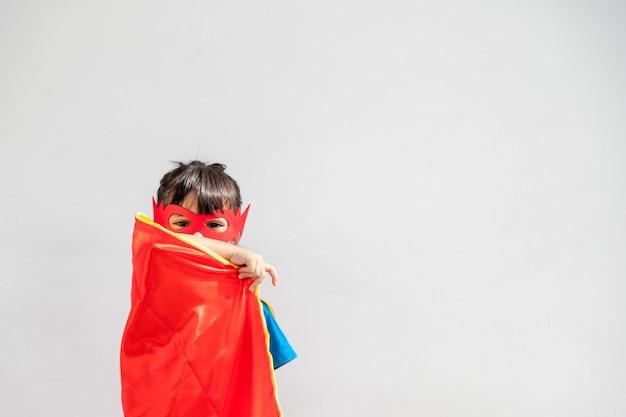 子供のコンセプト、白い背景でスーパーヒーローを演じる笑顔の女の子
