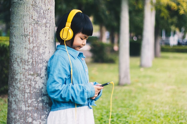Kids concept and technology - smiling girl with headphones listening to music