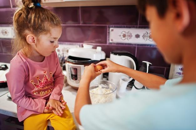 キッチンで料理をする子供たち、幸せな子供たちの瞬間。卵を割る。