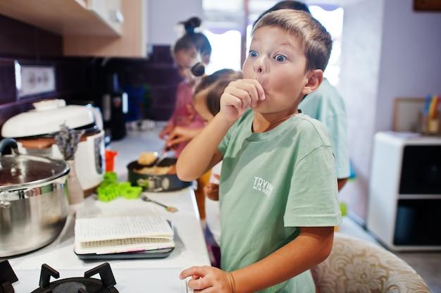 キッチンで料理をする子供たち、幸せな子供たちの瞬間。おいしい指をなめる!