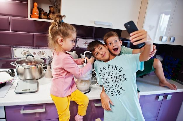 キッチンで料理をする子供たち、幸せな子供たちの瞬間。電話で自分撮りをする。
