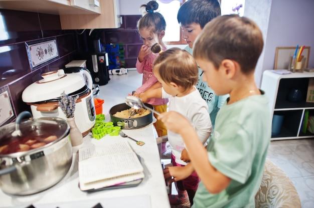 キッチンで料理をする子供たち、幸せな子供たちの瞬間。彼らはチーズケーキを準備しています。