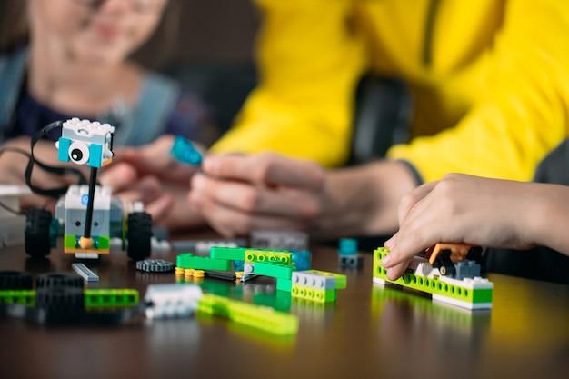 Kids creating robots with teacher. early development, diy, innovation, modern technology .