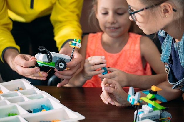 Kids creating robots with teacher. early development, diy, innovation, modern technology .