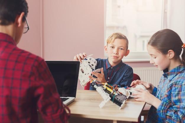 Kids creating robots with teacher