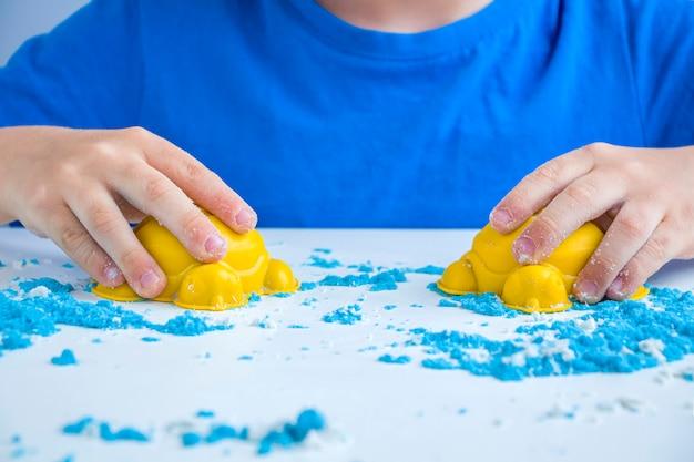 子供の創造性。家庭での子供の発達のための運動砂ゲーム。砂療法。カビを作る子供の手。セレクティブフォーカス、バックライト