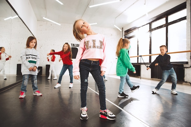 Kids at dance school. ballet, hiphop, street, funky and modern dancers over studio background.