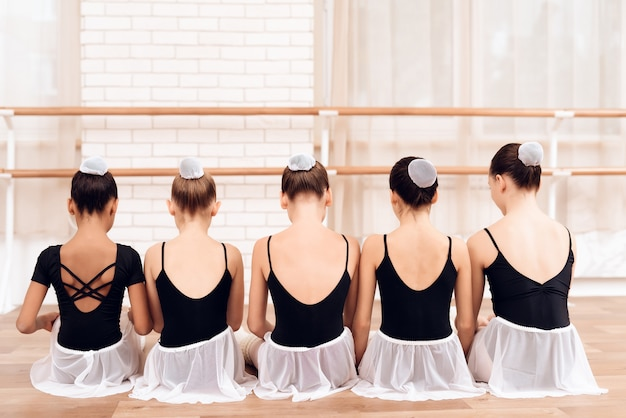 Kids dancers sitting in row with backs to camera.