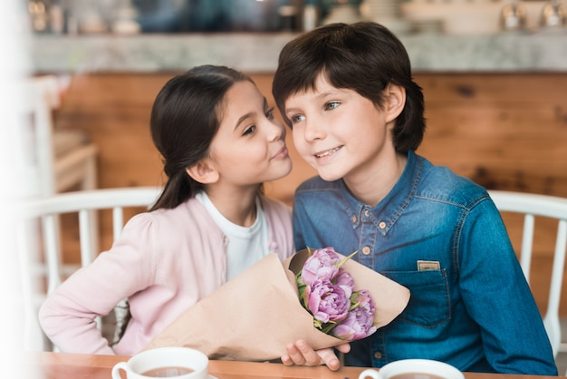 Kids' date in cafe boy gives flowers happiness.
