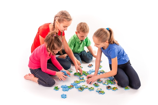 Kids of different age solving jigsaw puzzle together. teamwork, working together, solving problems concept
