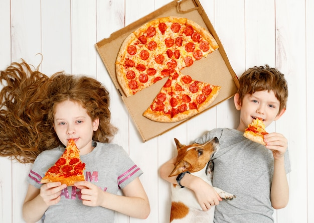 Kids and dog eating pepperoni pizza
