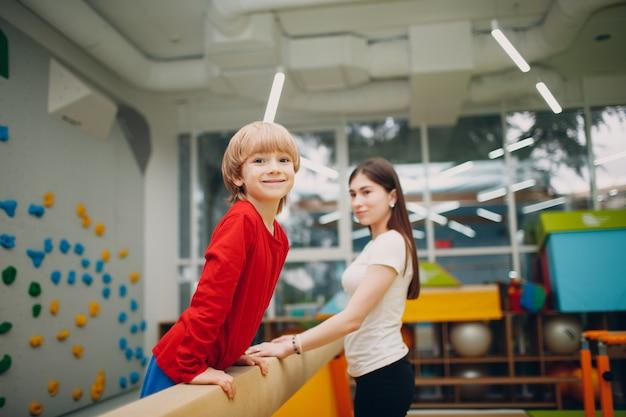 幼稚園や小学校の体育館で平均台体操をしている子供たち。子供のスポーツとフィットネスの概念。