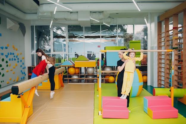 幼稚園や小学校の体育館で運動をしている子供たち。子供のスポーツとフィットネスの概念。
