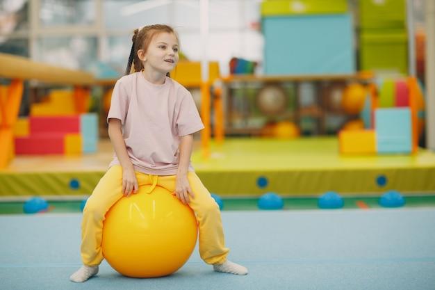유치원이나 초등학교 어린이 스포츠 및 피트니스 개념에서 체육관에서 큰 공 운동을하는 아이
