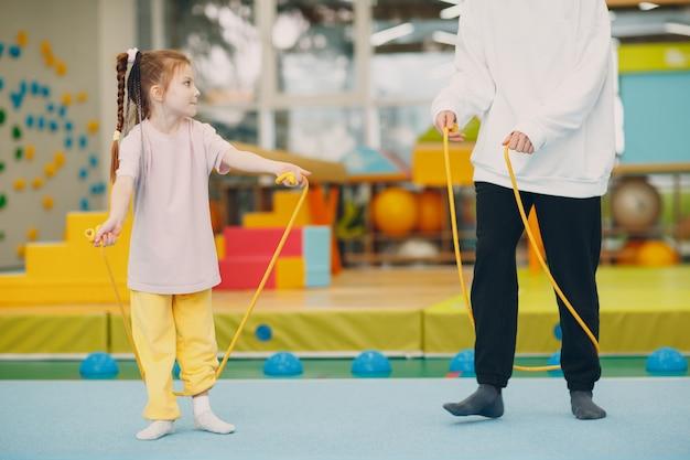 幼稚園や小学校の体育館で縄跳びをしながら運動をしている子供たち。子供のスポーツとフィットネスの概念。