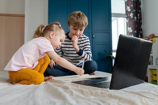 집에서 노트북을 사용하여 숙제를하는 아이들