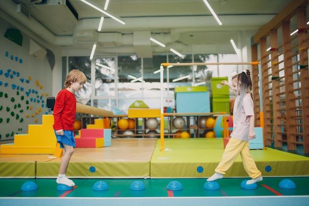 유치원이나 초등학교 어린이 스포츠 및 피트니스 개념에서 체육관에서 발 다리 운동을위한 마사지 고슴도치를하는 아이들