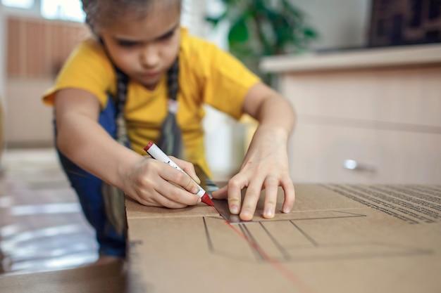 온라인 배달 후 골판지 상자가있는 종이 집을하고 함께 노는 아이들