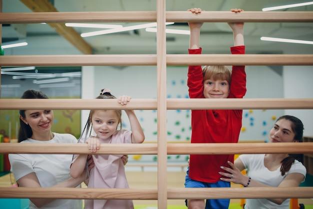 유치원이나 초등학교 어린이 스포츠 및 피트니스 개념 체육관에서 스웨덴어 벽 운동을하는 아이들