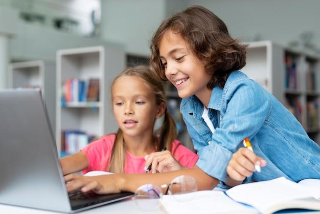 ノートパソコンで宿題をしている子供たち