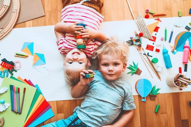 Дети рисуют и делают поделки детей с развивающими игрушками и школьными принадлежностями для творчества