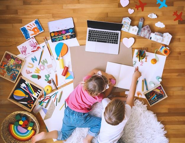自宅でオンラインアートクラスを使って工芸品を描いたり作ったりする子供たち