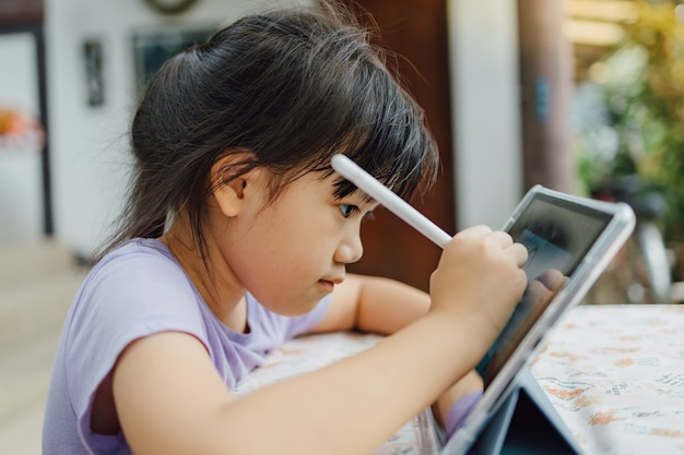 Kids drawing on digital smart tablet technology concept for new  normal of learning style