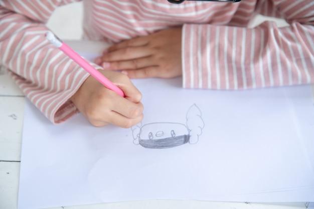 テーブルの上に自分自身を描く子供たち