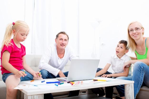 ソファで幸せな親と一緒に描く子供たち