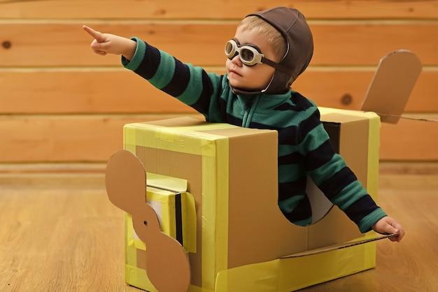 子供の夢。小さな男の子の子供は、段ボールの飛行機、子供時代に遊びます。