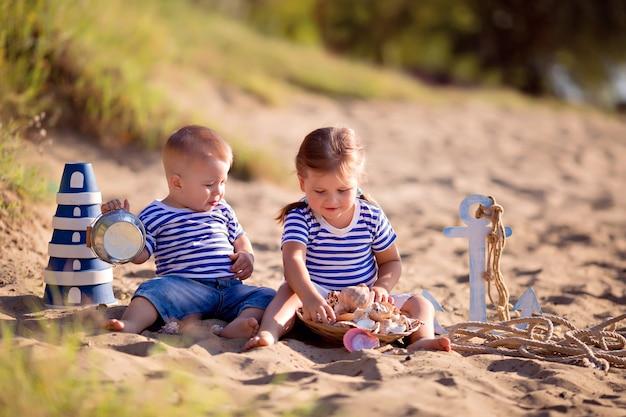 바다 조개와 모래 해변에서 선원으로 옷을 입고 아이들