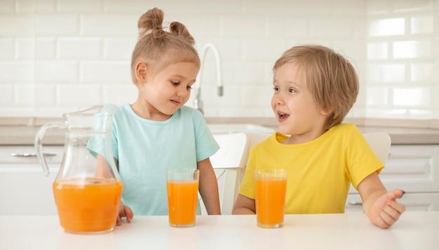 自宅でジュースを飲む子供たち