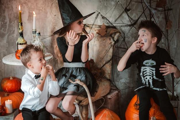 Дети едят сладости на хэллоуин на костюмированной вечеринке