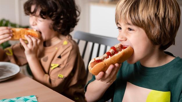 Kids eating hot dogs together