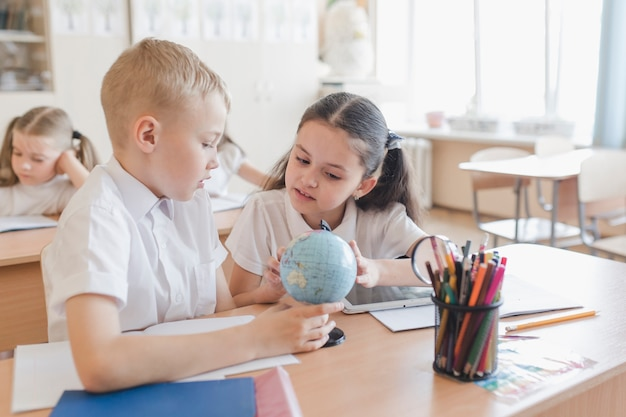Kids examining globe at lesson