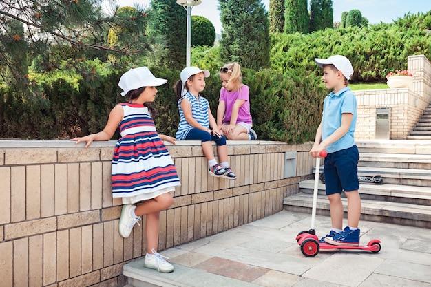 키즈 패션 개념. 공원에서 포즈를 취하는 십 대 소년과 소녀의 그룹. 어린이 화려한 옷, 라이프 스타일, 유행 색상 개념.
